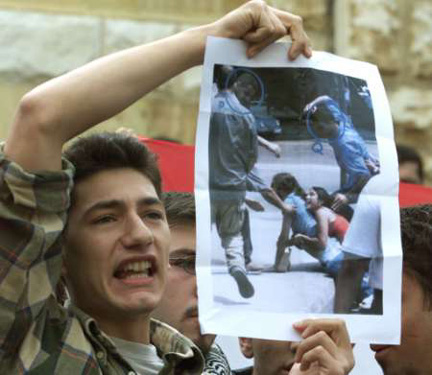 A Lebanese student, during a sit-in, holds a picture of his brutalized  colleagues in a  previous demonstration against Syrian occupation
